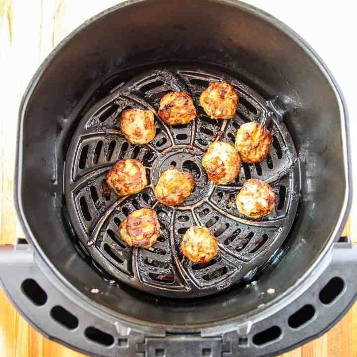An air fryer basket with cooked turkey meatballs.