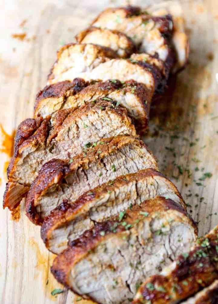 Slices of air fried pork tenderloin on a wooden cutting board.