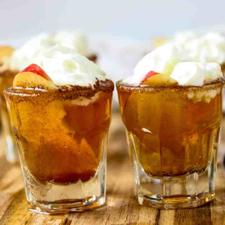 Two shot glasses with apple pie shooters and topped with whipped cream.