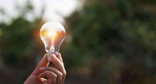 hand holding light bulb in nature background. concept solar ener