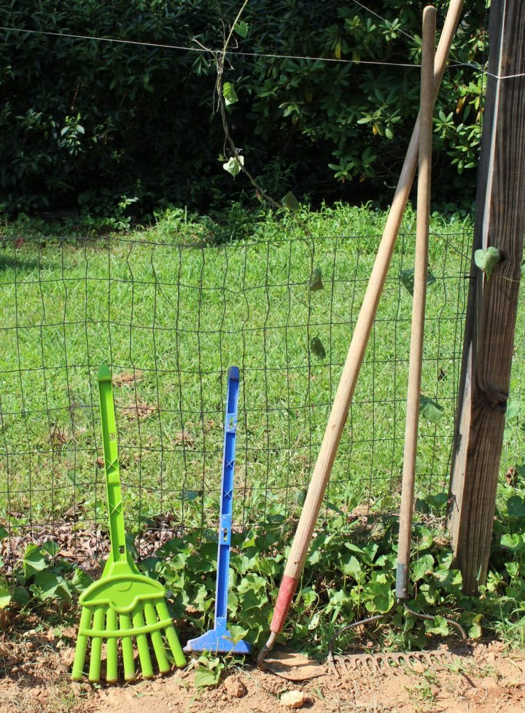 child garden tools next to regular gardening tools leaning on a fence