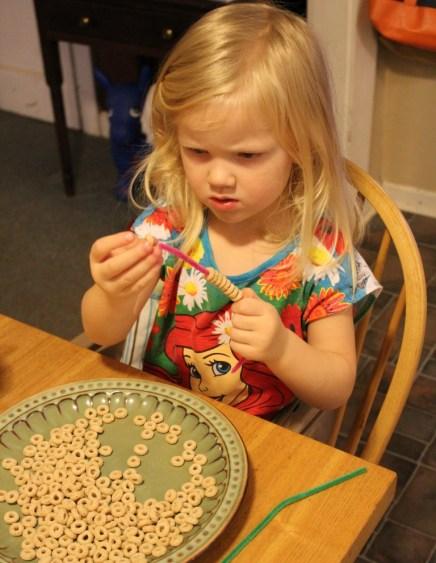 little girl making cereal bird feeder