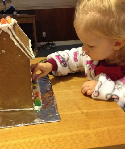 little girl decorating gingerbread house