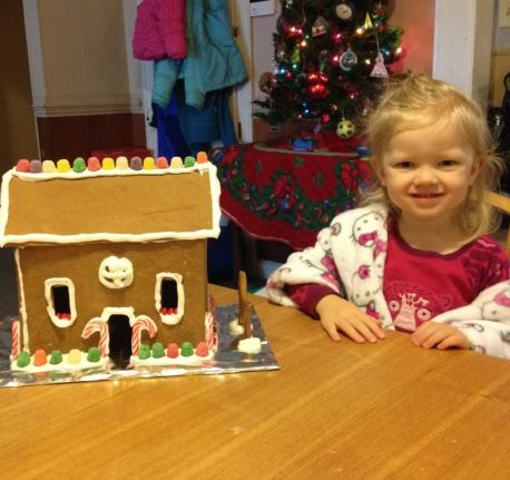 girl posing with gingerbread house