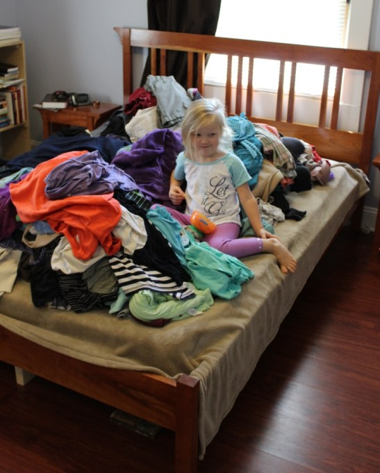 little girl in a pile of clothes in a bed