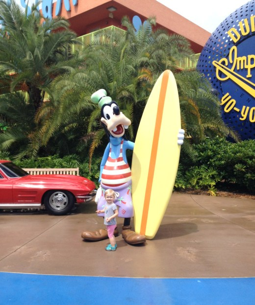 little girl posing with surfer goofy statue