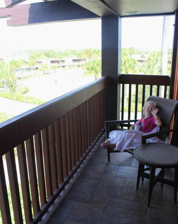 little girl sitting in a chair on the baclony