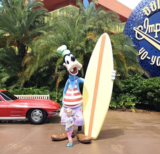 little girl standing in front of surfer goofy statue
