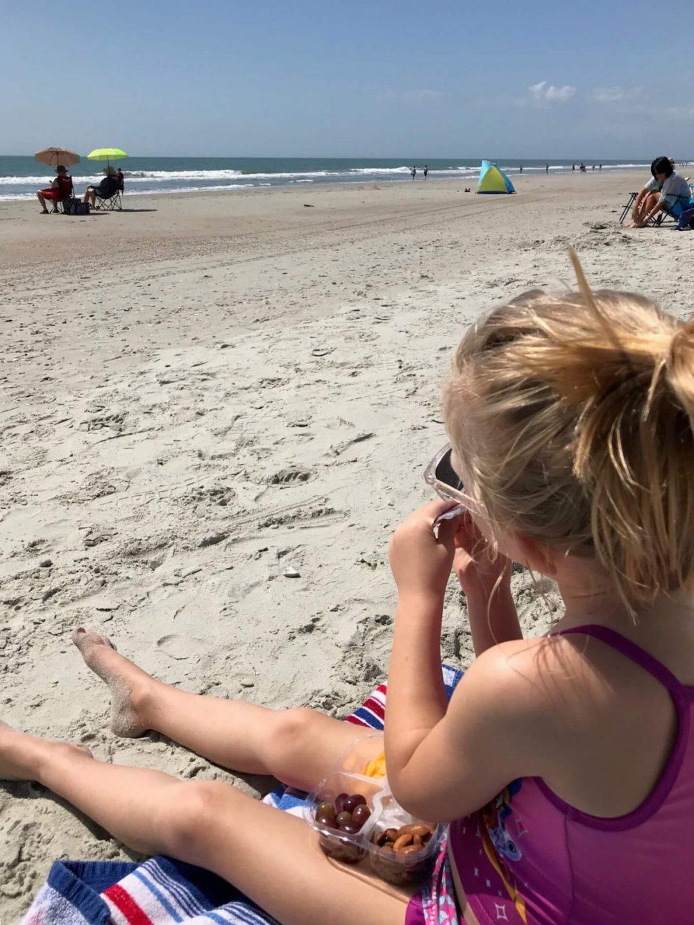little girl enjoying a snack on the beach