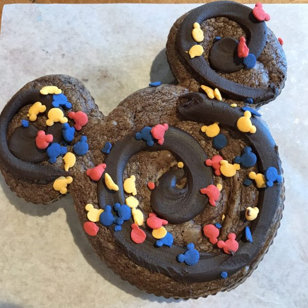 brownie treat in the shape of mickey mouse with mickey mouse sprinkles