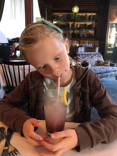 little girl drinking a blueberry lemonade