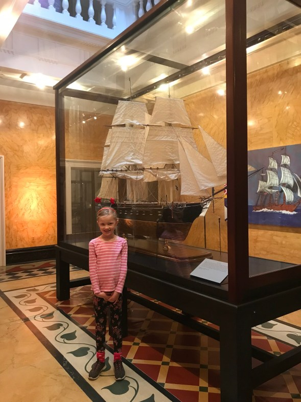 little girl in front of a display of ship replica