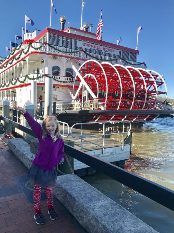 little girl in front of a ferry boat