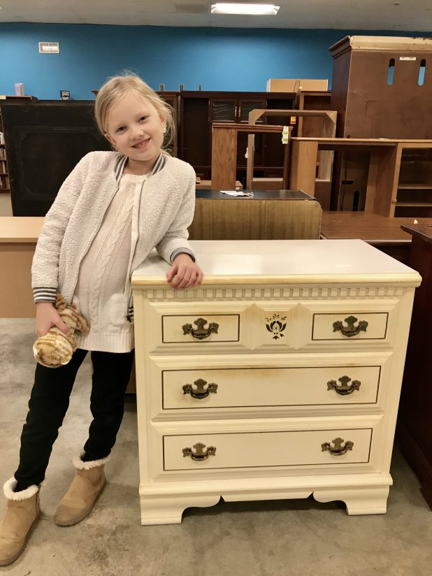 little girl standing by the chest of drawers before the makeover