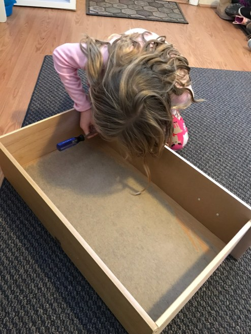 little girl installing the drawer hardware