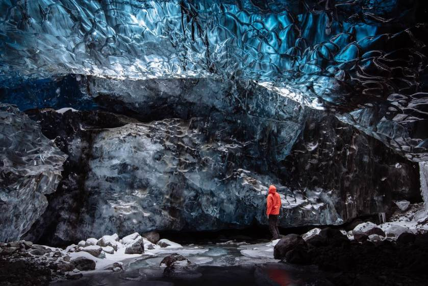 Person in orange jacket staring up at ice cave