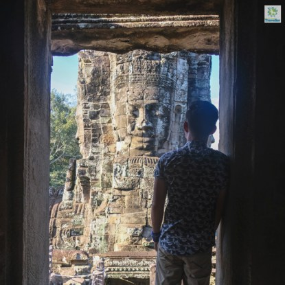 At a window at the upper tier of Bayon temple, with a stone face on the background.
