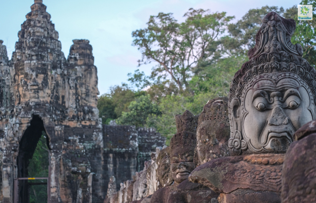 The Avalokiteshvara face tower on the left and statues of Asura, Gopuram, and some demons balustraded on the bridge to the South gate of Angkor Thom.