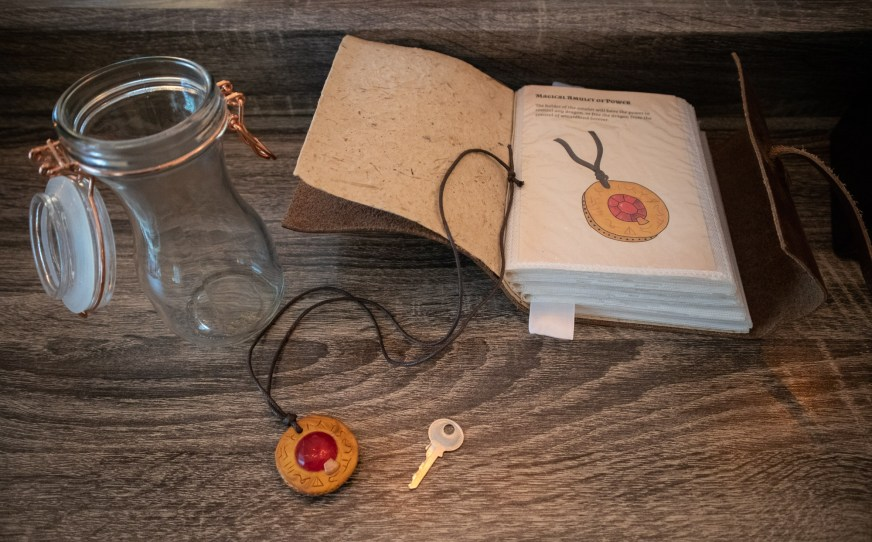 spell book and magical amulet for wizard escape room
