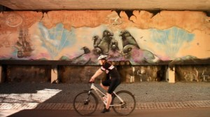 a cyclist pedals past some of Helsinki's street art