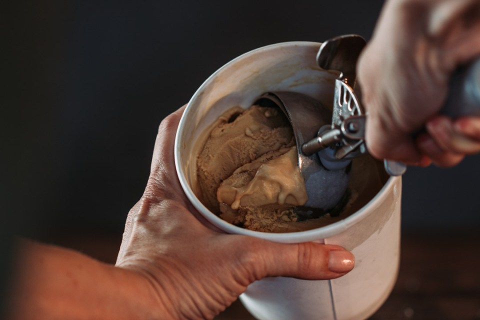 scooping caramel gelato out of container