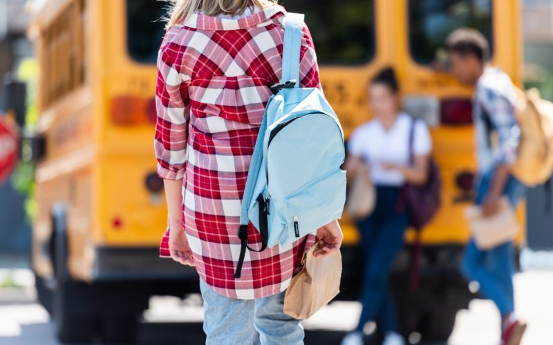 rear view of teen schoolgirl walking to classmates leaning on school bus