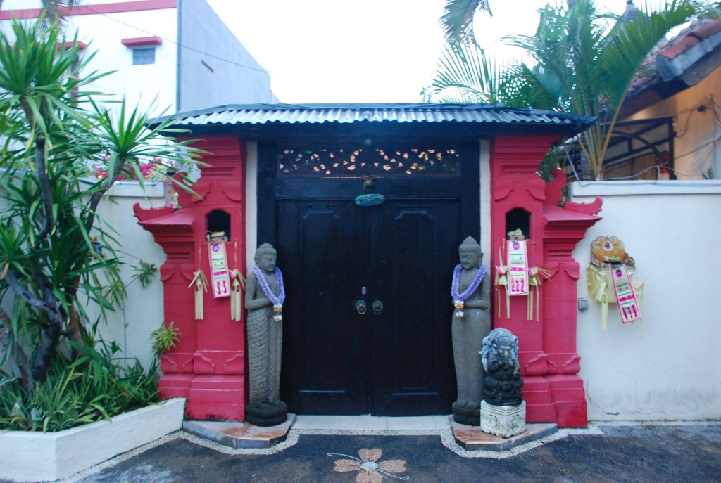 doorway in Bali with statues and flowers