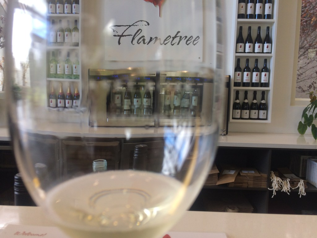 Flametree winery glass and wines behind on shelf