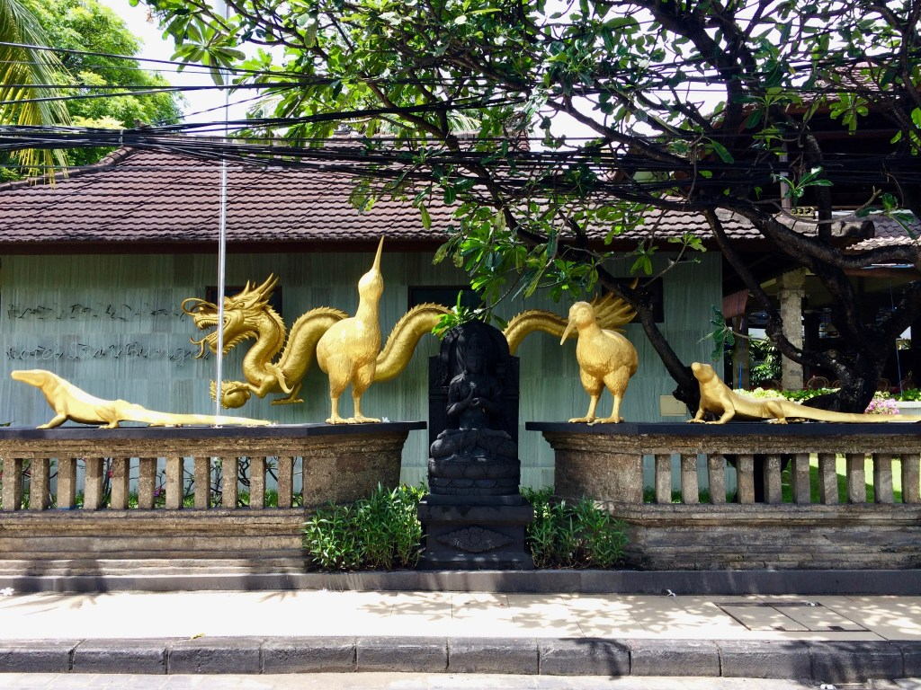 golden statues on a fence in Bali