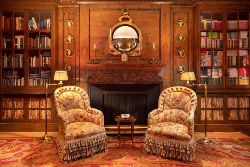 wood-paneled-library-fireplace-chairs-books-renzo-mongiardino-1-sutton-place-sothebys