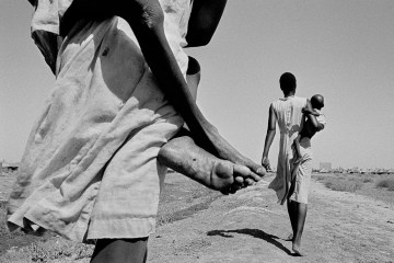Front Cover. South Sudanese displaced. Most of the malnourished children are too weak to walk the 300m to the feeding center and have to be carried there. Kosti. Sudan. 1988 © John Vink_Magnum Photos