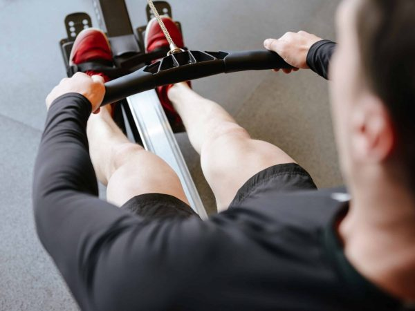 Back view of Athletic man which using rowing machine in gym
