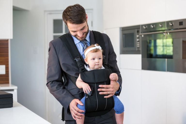 Businessman carrying daughter by table at home