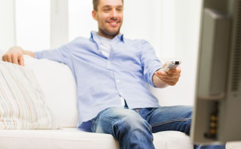 close up of man with tv remote control at home