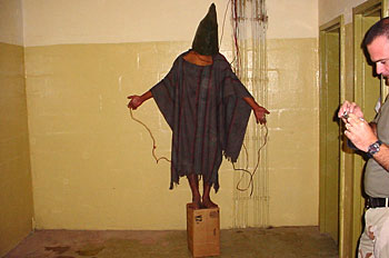 """Photo in the Public Domain  November 2003 - Hooded detainee with wires attached to hands and genitalia stands on a box; the detainee was told that he would be electrocuted if he fell off the box. Staff Sgt. Ivan """"Chip"""" Frederick, at right, clips his fingernails."""