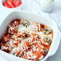Finished Cheesy Baked Meatballs just out of the oven and still in a white casserole dish.