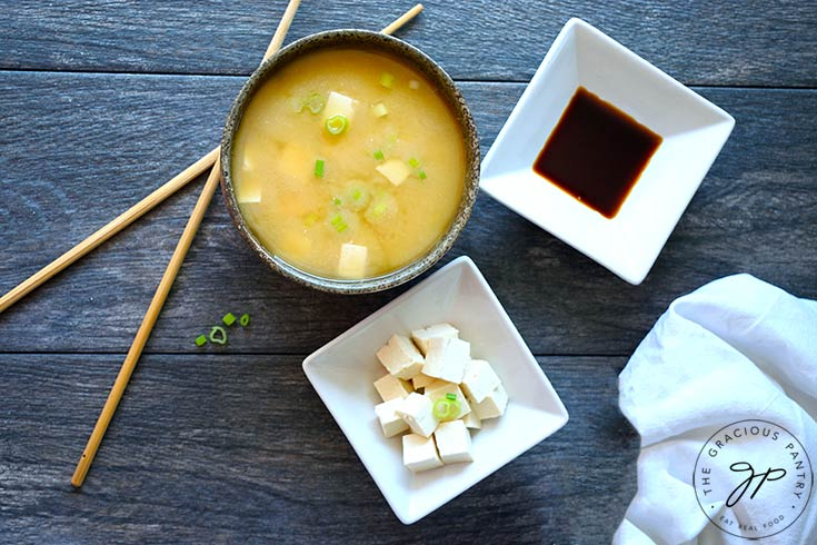 Componants of this Miso Soup Recipe in separate bowls. Tamari, cubed tofu, and a finished bowl of soup on a gray background. Chopsticks lay to the side.