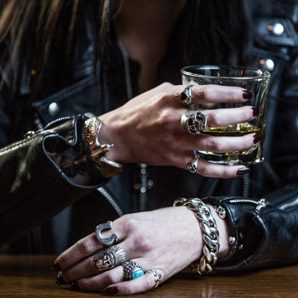 A Woman With Painted Nails Wearing Leather Jacket And Silver Jewellery Holding Gl Of