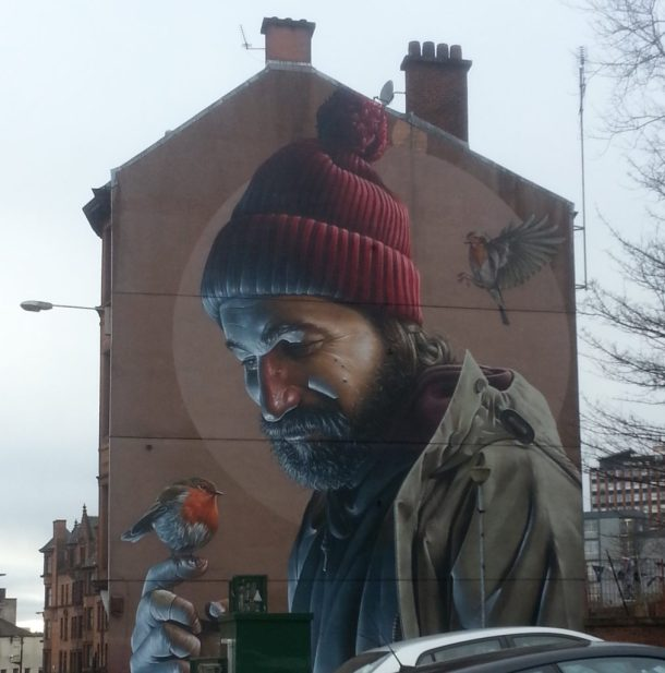Artwork on a building. A man with a small bird perched on his finger