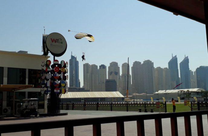 Tandem skydivers landing next to Dubai buildings