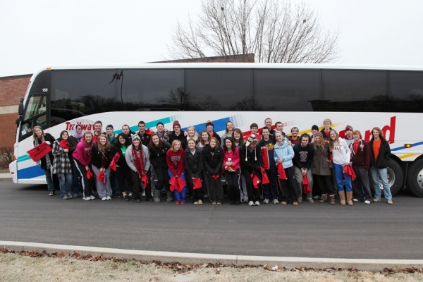 Benedictine College students pose by one of four buses that was home for nearly a week.