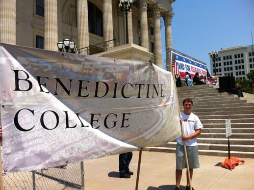 Brock Martin holds the Benedictine College banner at stage right at the Topeka, Kansas, Rally for Freedom.