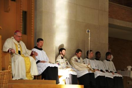 The Archbishop and altar servers pray after communion.