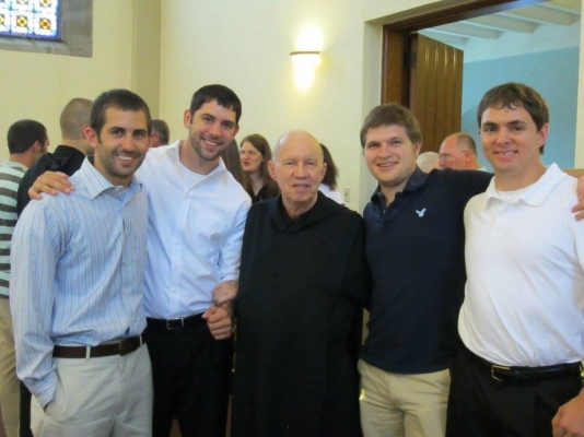 Father Bruce with students of Benedictine College, where he serves as confessor for years.