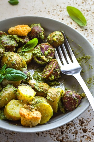 Pesto Potato Salad in a grey plate with basil topping