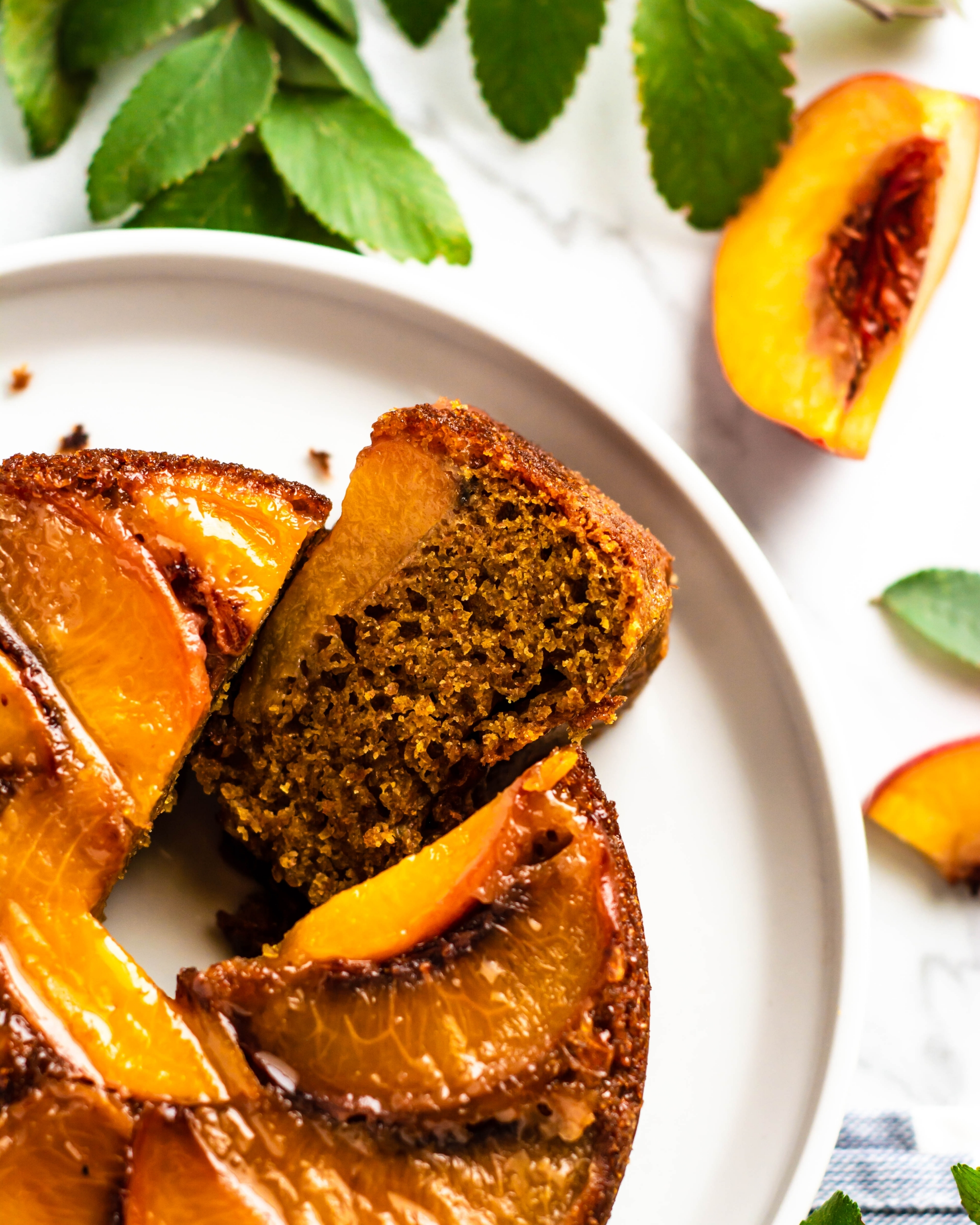Upside down peach cake with a slice open