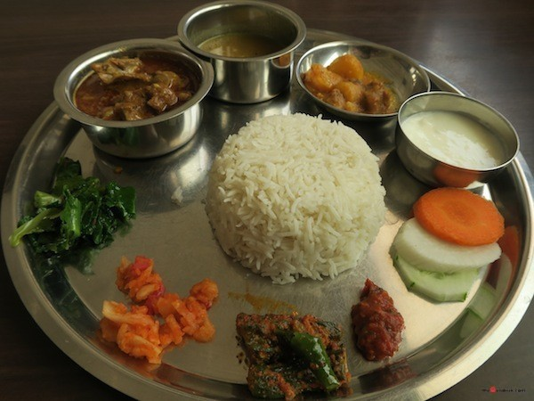 Thakali Khana set- Rice, Mustang beans daal, Mutton curry, Seasonal vegetable curry, Stir-fried spinach, Grated Radish pickle, Timur-Tomato chutney, Bitter guard pickle and Yoghurt