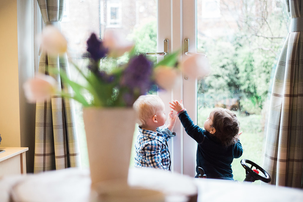 two babies at a patio doors