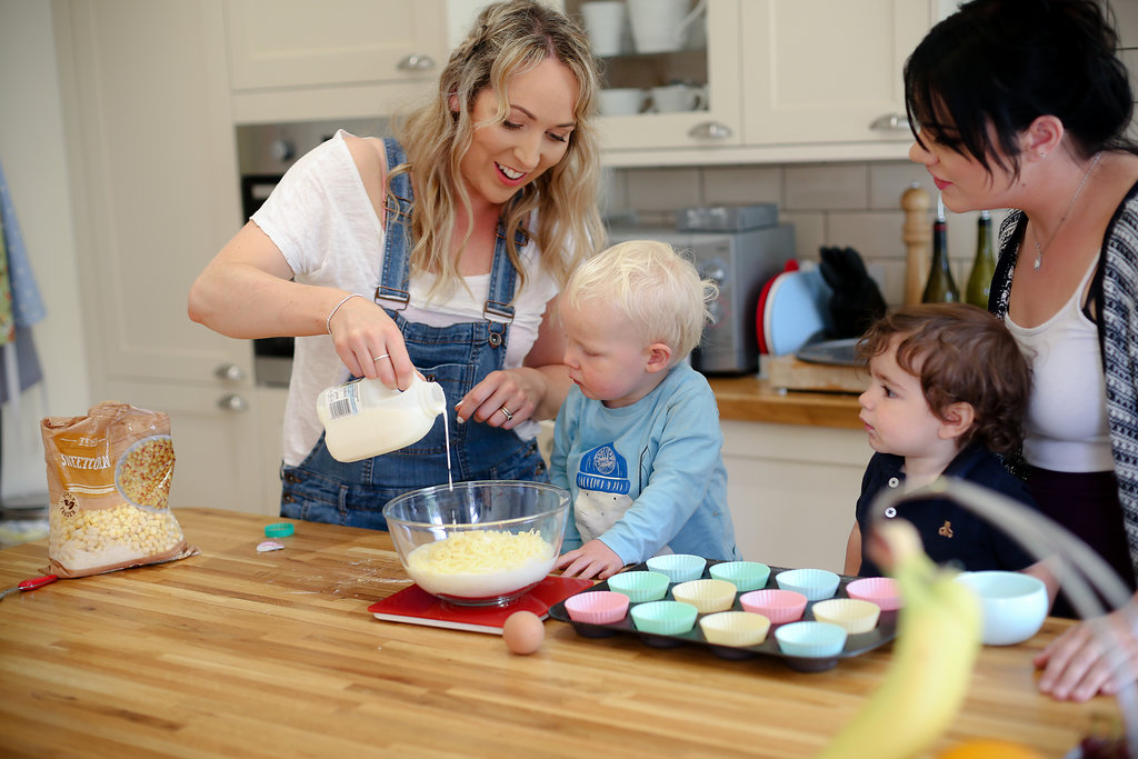 two mums cooking with their two boys in the kitchen