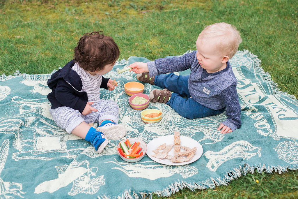 two toddlers eating hummus and dip at a picnic